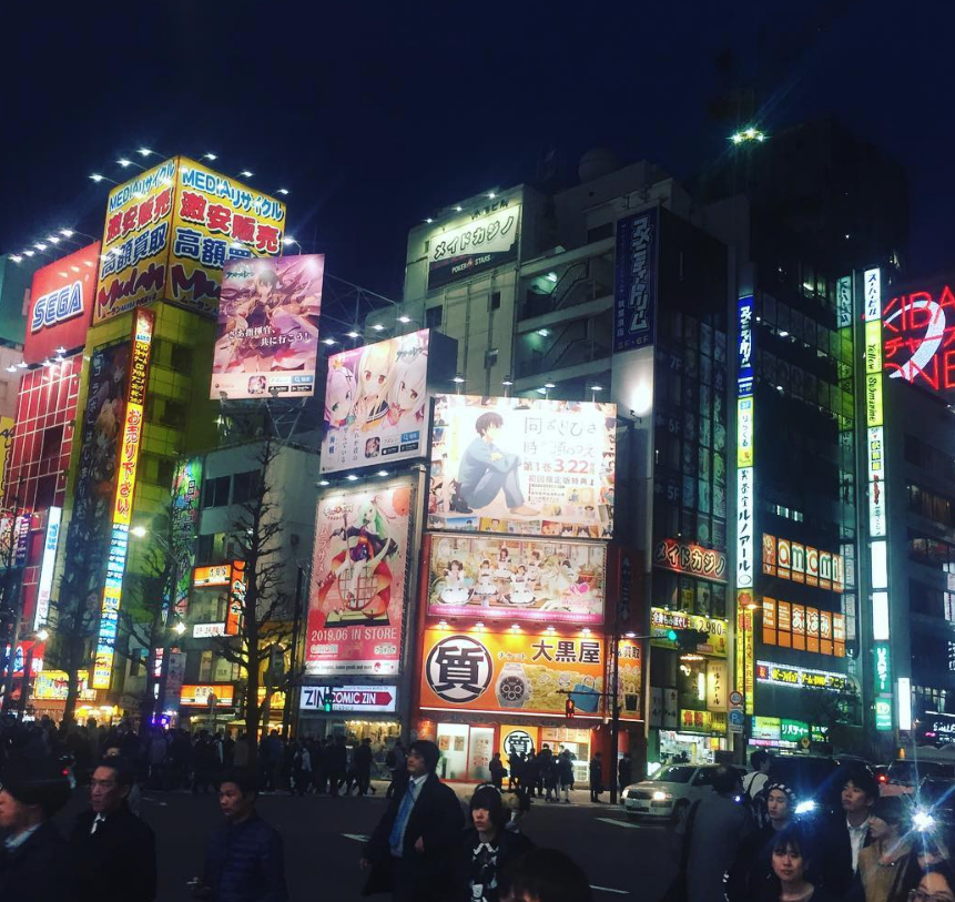 A crossing in Akihabara, where manga and anime release banners shine with the light of a million suns