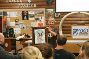 Linda receiving the gift of a sketch which incorporates our logo into a full body elephant