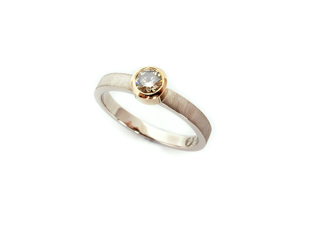 Here again understated elegance, a solitaire champagne diamond set in the customers own recycled heirloom rose gold bezel, with 9ct grey gold band with a velvet matte finish.