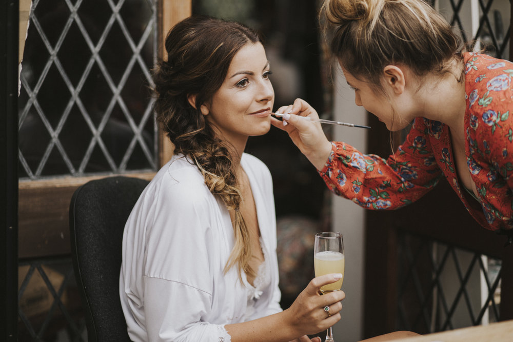 make up artist putting makeup on bride