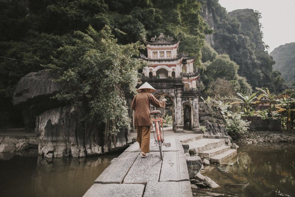 Monk on bridge in Tamcoc