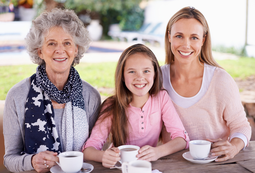 Three generations of females drinking tea outdoors and smiling at the camera