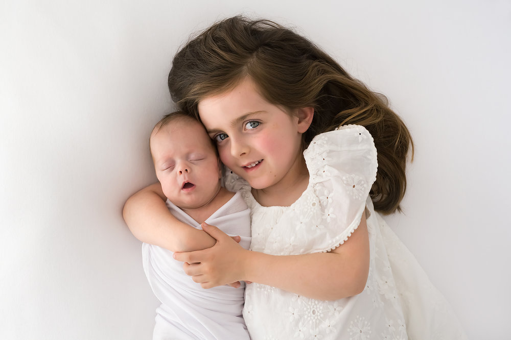 A professional photo of a girl cuddling her newborn baby sister during a photography session in Melbourne