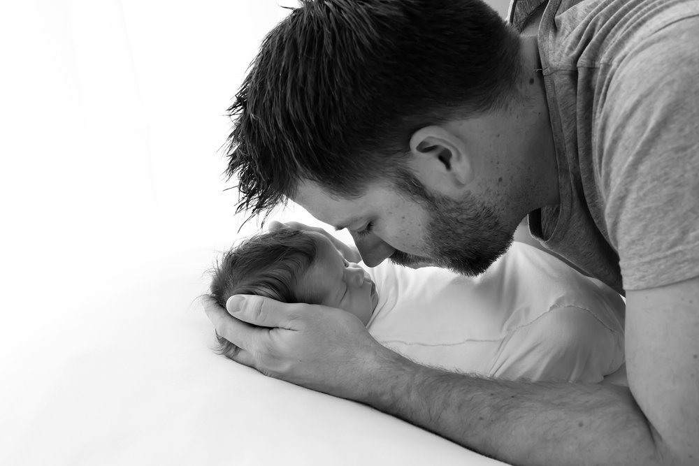 A candid moment with a new dad holding his baby girl while taking baby photos in Melbourne