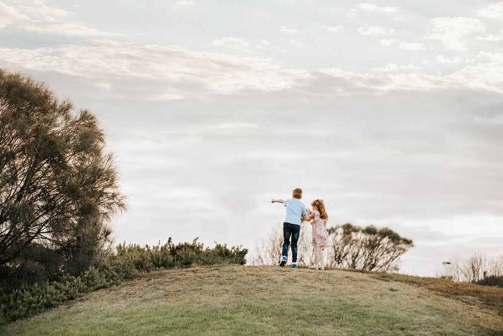 A candid photograph of two children standing at the top of a hill in Melbourne.  Taken by a professional photographer.