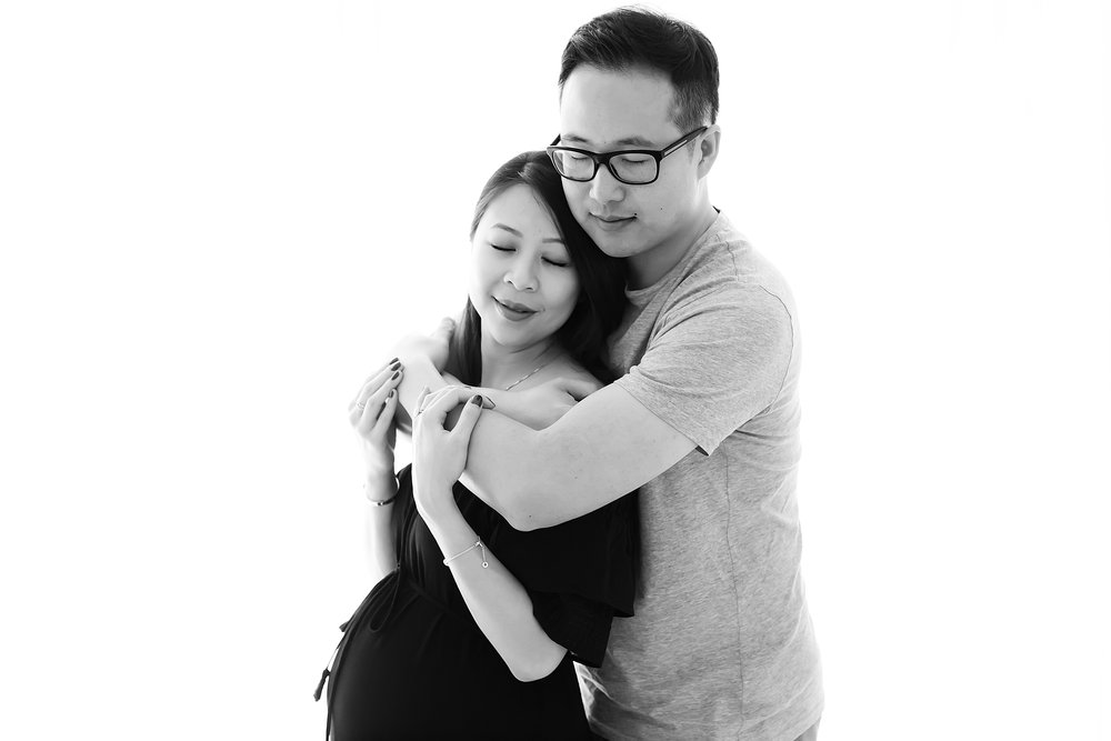 Black and white photo of couple embracing during their pregnancy photography session in Melbourne