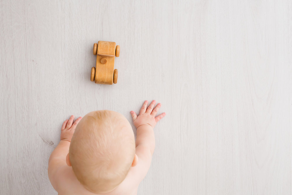 Image from above of baby crawling towards wooden car during baby milestone photography session in Melbourne