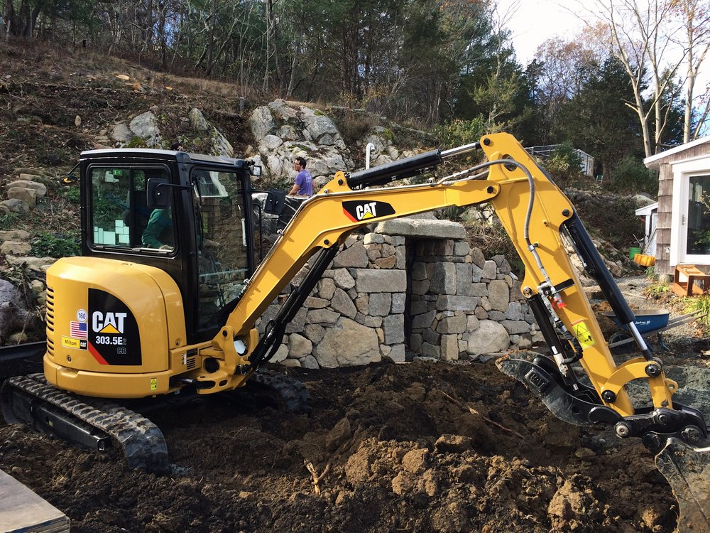 November 2017  Bringing in a machine to set the huge mantel stones across door way and to make quicker work of bringing in soil for back fill