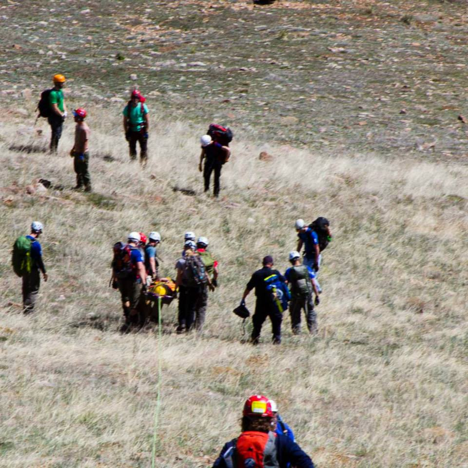 Patient with yellow helmet in litter is being lowered to the bottom of the hill (away from the camera) following his rescue after a paragliding accident.
