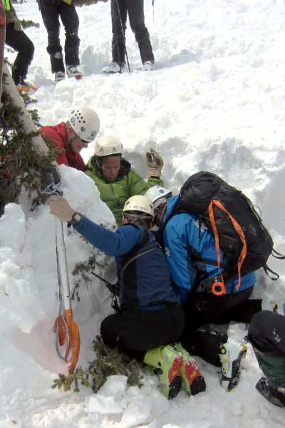 Avalanche search scenario: Rescuers (blue & red jackets) splinting a simulated broken leg of a (simulated) partially buried avalanche accident victim (green jacket). Legs of regional scenario evaluators standing behind. Photo Greg Foley, Grand County Search and Rescue, reproduced with permission.