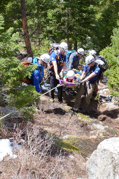Scree evacuation scenario: Rescuers performing scree evacuation during RMRG's 2013 re-accreditation test. Rescuers lift the litter borne (simulated) injured party and lean against the tension of a belayed lowering rope.