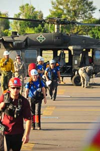 Rescuers unloading from a National Guard helicopter after flood deployment. Photo credit, Dave Zader.