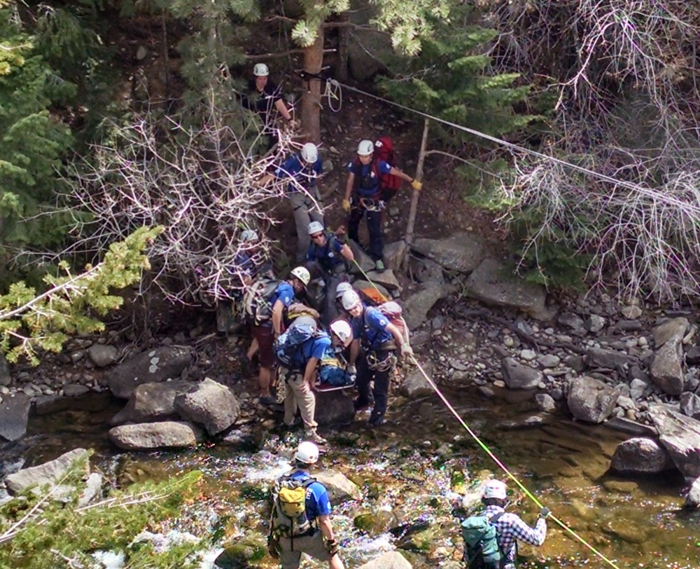 Rescuers carrying the litter borne patient across Boulder Creek at a low-water crossing.