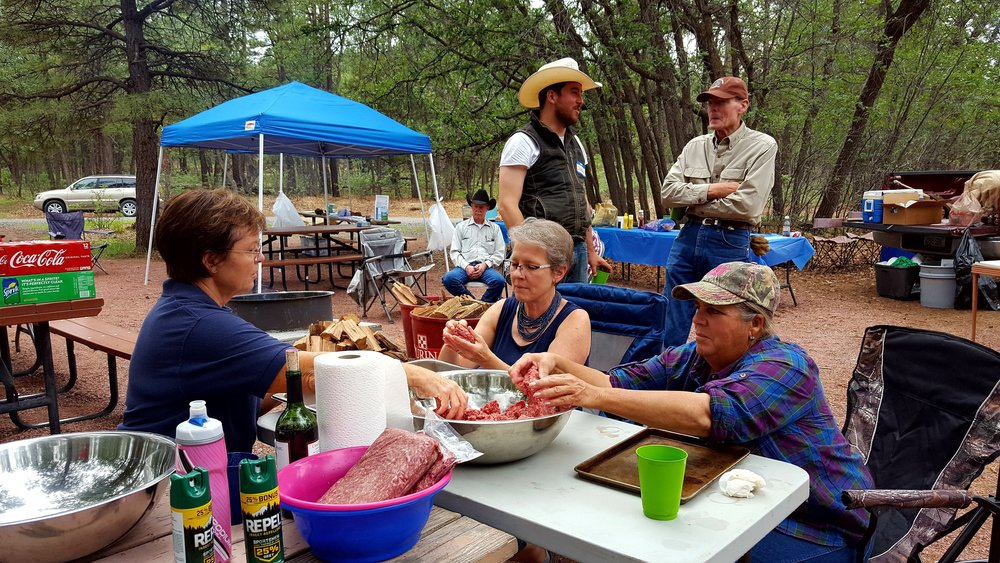 Judy Prosser, Gail Lowe, and Kit Metzger shape the beef patties for hamburgers. Jim Parks is seated in the background, and Jeremy Krones and Stephen Williams chat.  Photo by Denise Hudson.