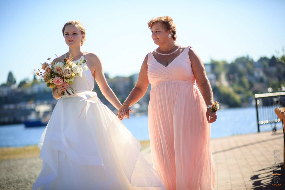 Bride and Mom hand in hand as they walk down the aisle.