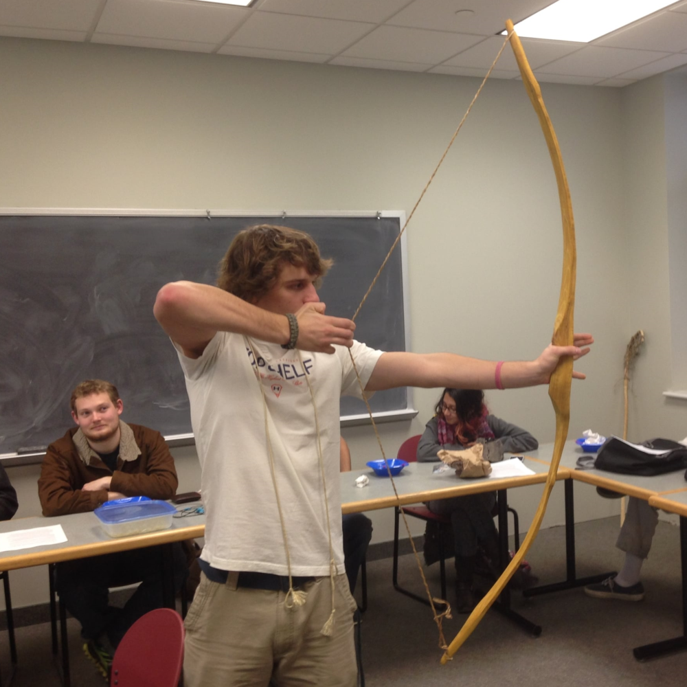 Student drawing his first homemade bow.