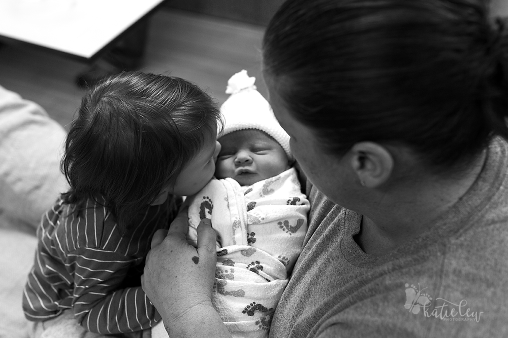 sister gives baby a kiss birth