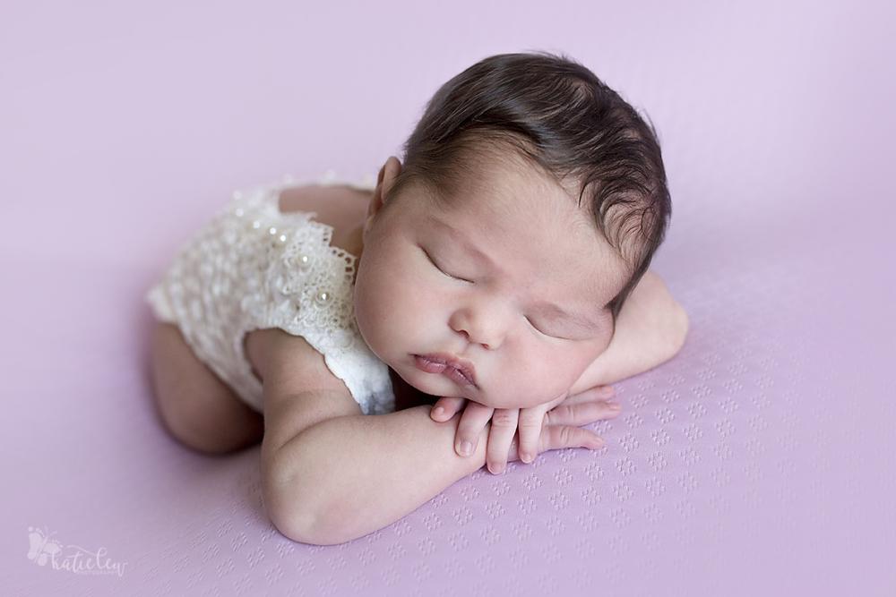 head on hands pose newborn baby girl