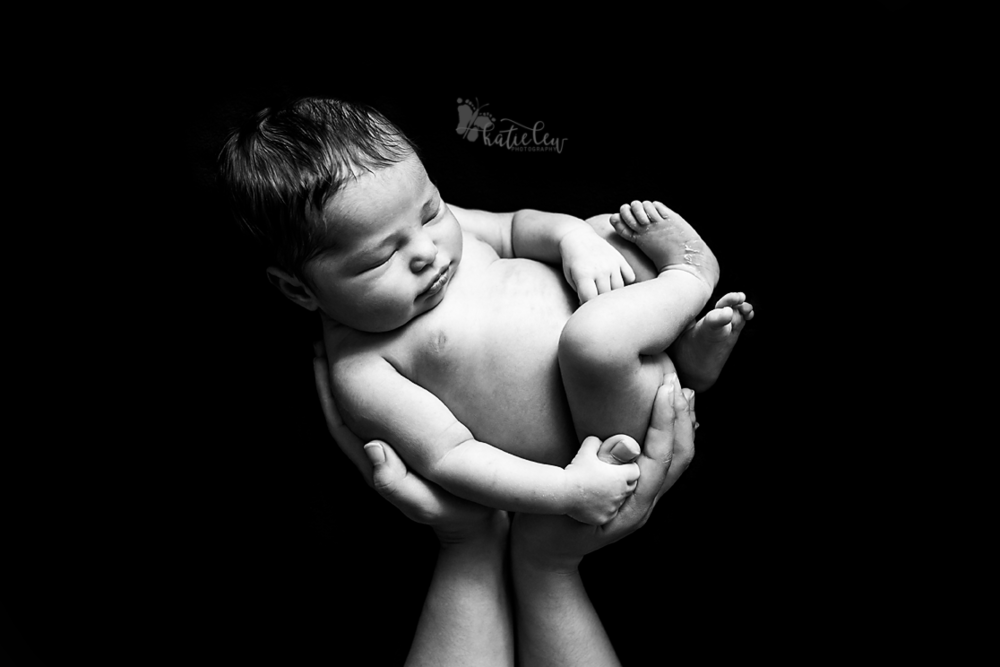baby in mom's hands on black background