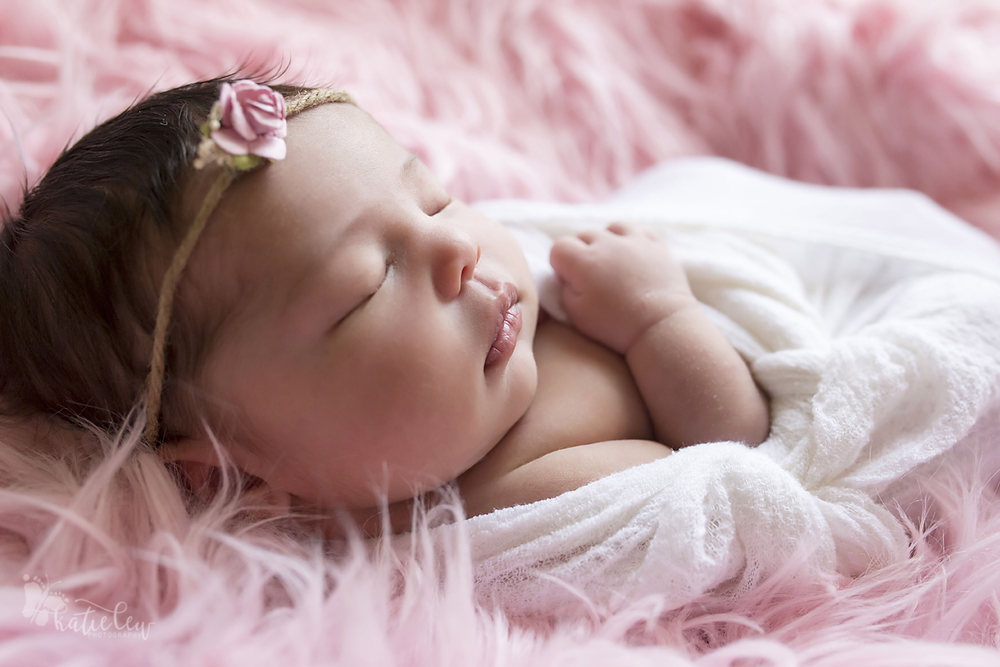 newborn girl wrapped in white on pink fur