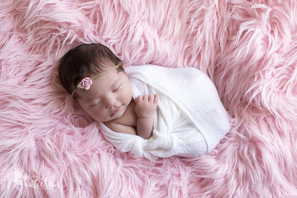 newborn girl on pink fur wrapped