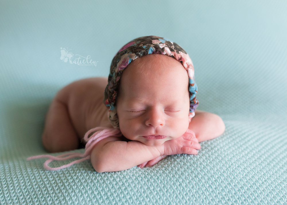 newborn baby twin girl wearing a floral bonnet lying on a blue blanket