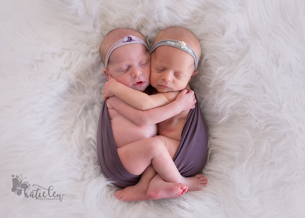 Twin baby girls hugging each other and wrapped in purple