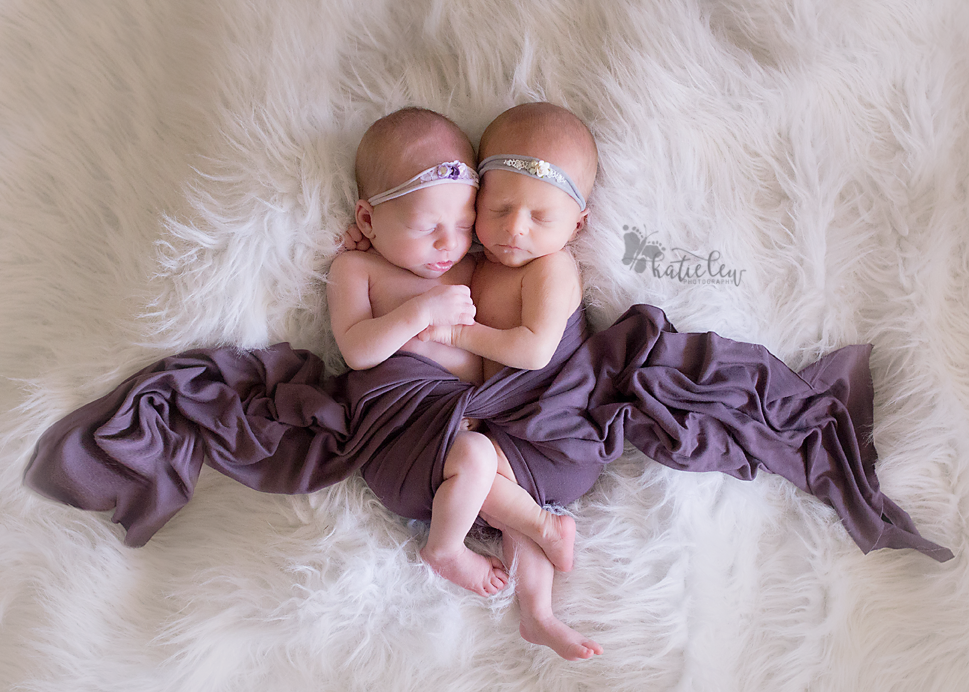 A delicate image of two baby girls with purple cloth