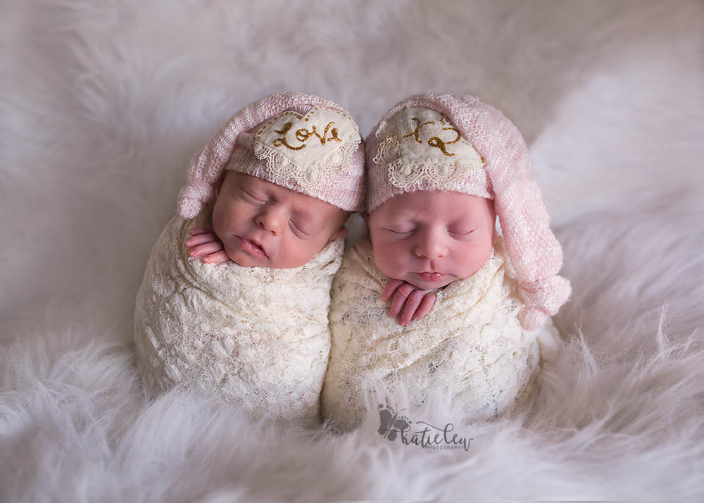 Twin baby girls with hats that say love times two