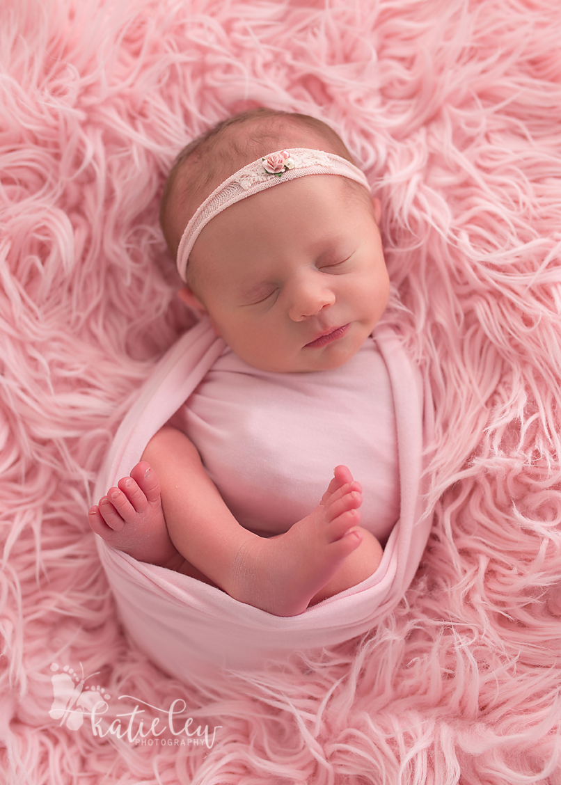 newborn baby girl is wrapped all in pink and nestled in pink fur