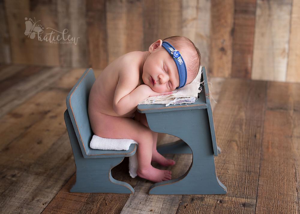 newborn baby girl sitting at a desk