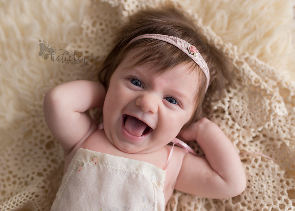 baby girl gives photographer a huge smile at her session in stillwater, oklahoma