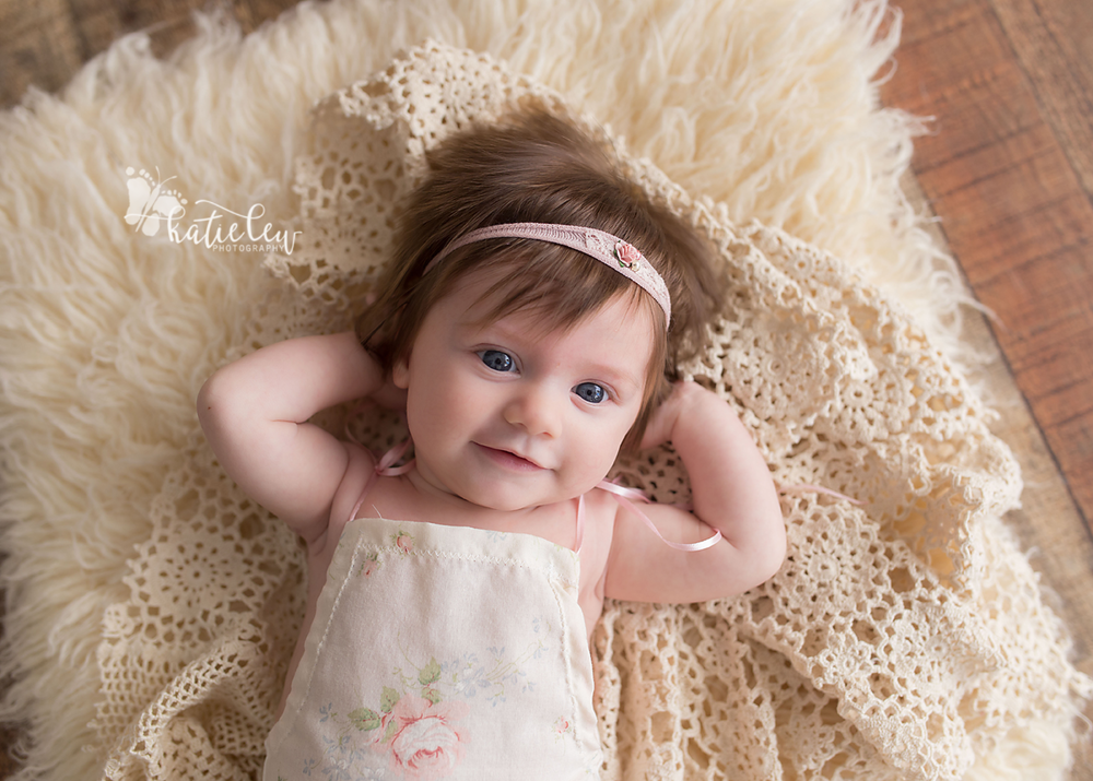 Little girl laying on lace and fur and wearing a cute rose romper