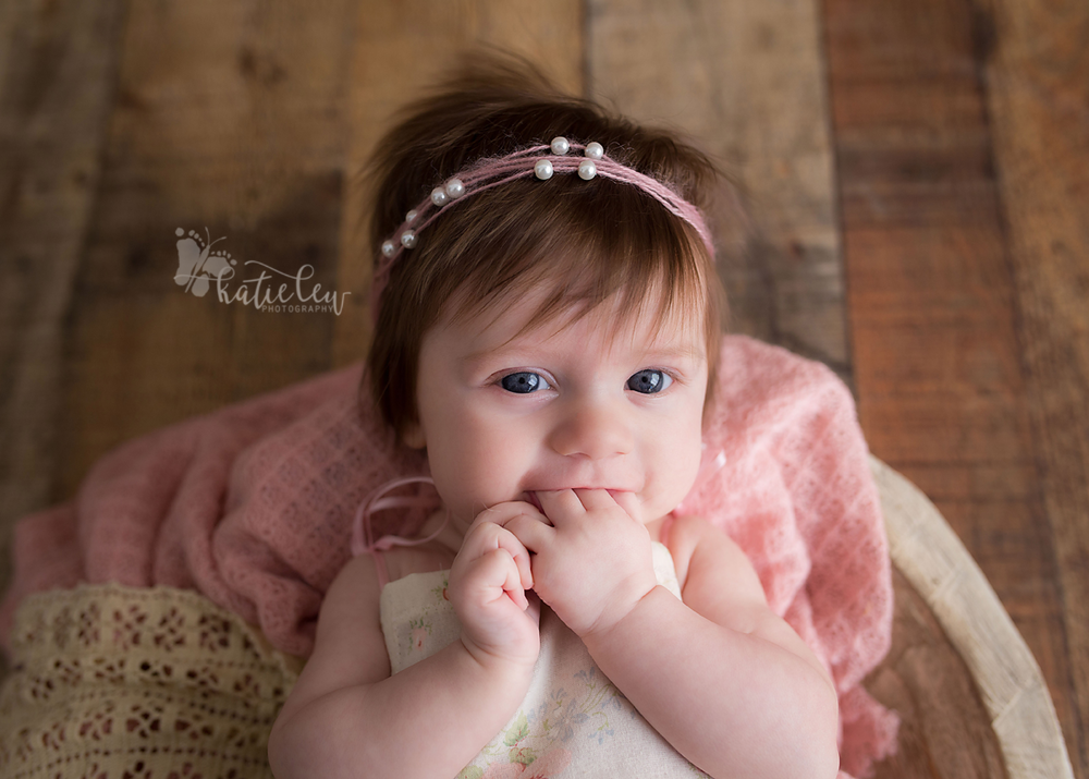 Baby girl loves chewing on her fingers at her photography session in stillwater, oklahoma
