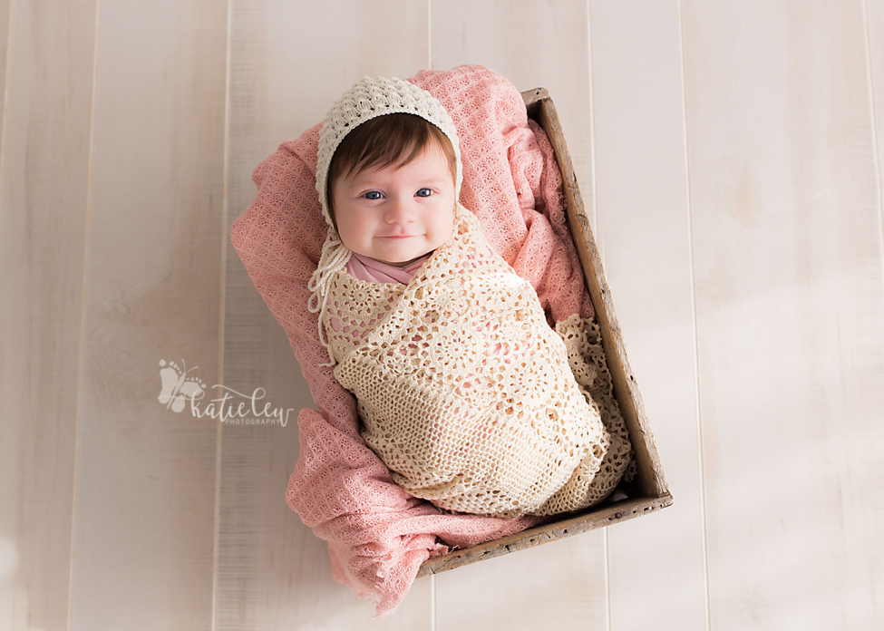 A sweet smiling baby wrapped in lace