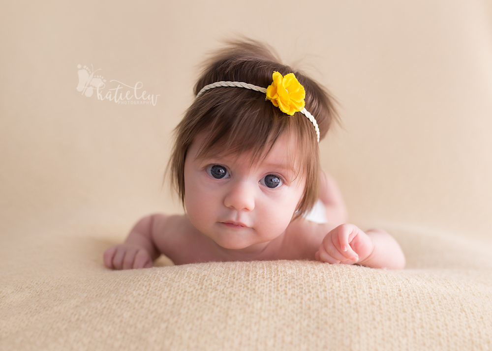 baby girl with a head full of hair wearing a yellow flower