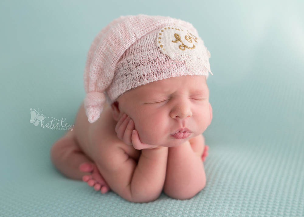 A side view of froggy pose with a baby girl wearing a pink hat.