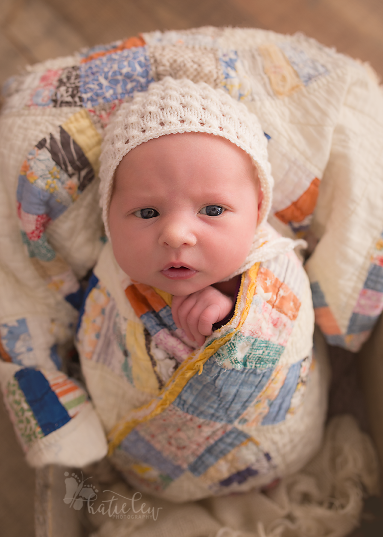 newborn girl wrapped in a beautiful quilt