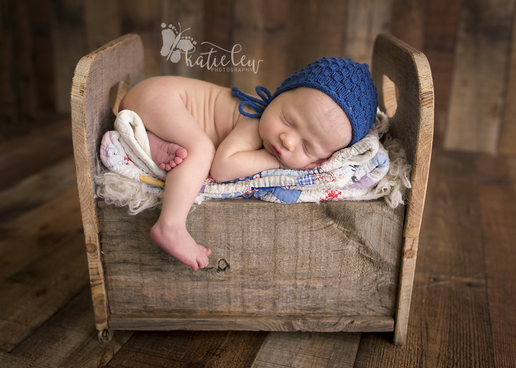 Newborn baby boy snuggled asleep up on a baby bed