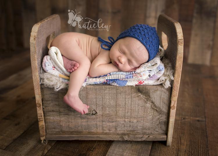 Newborn baby boy snuggled asleep up on a baby bed