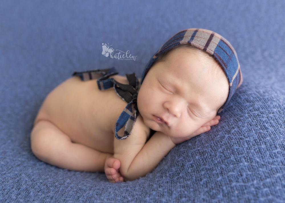 Baby boy wearing a plaid bonnet