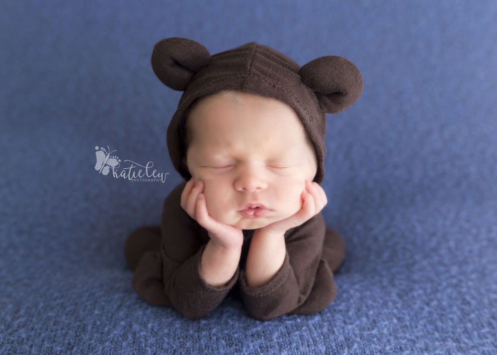newborn baby dressed in an adorable teddy bear outfit