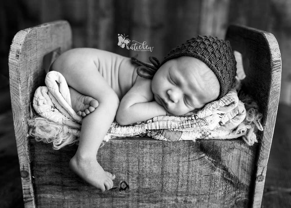 newborn baby boy laying on a bed of soft quilts