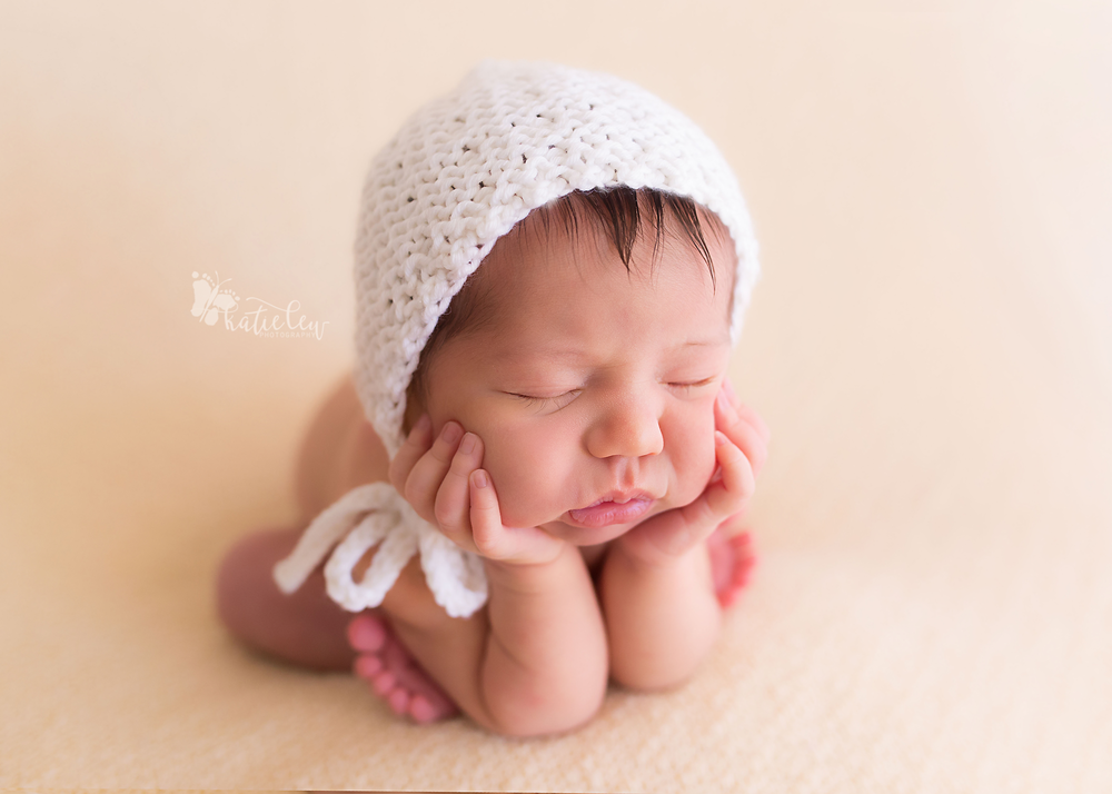 Newborn photography froggy pose with white bonnet