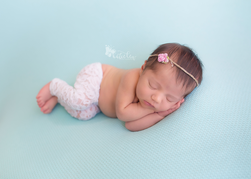 Newborn baby girl snuggled on a blue blanket