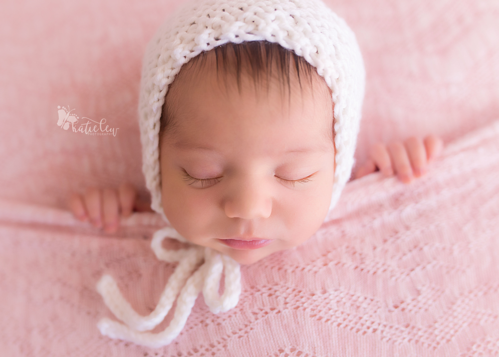 Newborn photography baby girl tucked in wearing a white bonnet