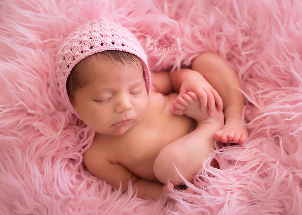 Sweet baby girl nestled in pink fur wearing a pink bonnet