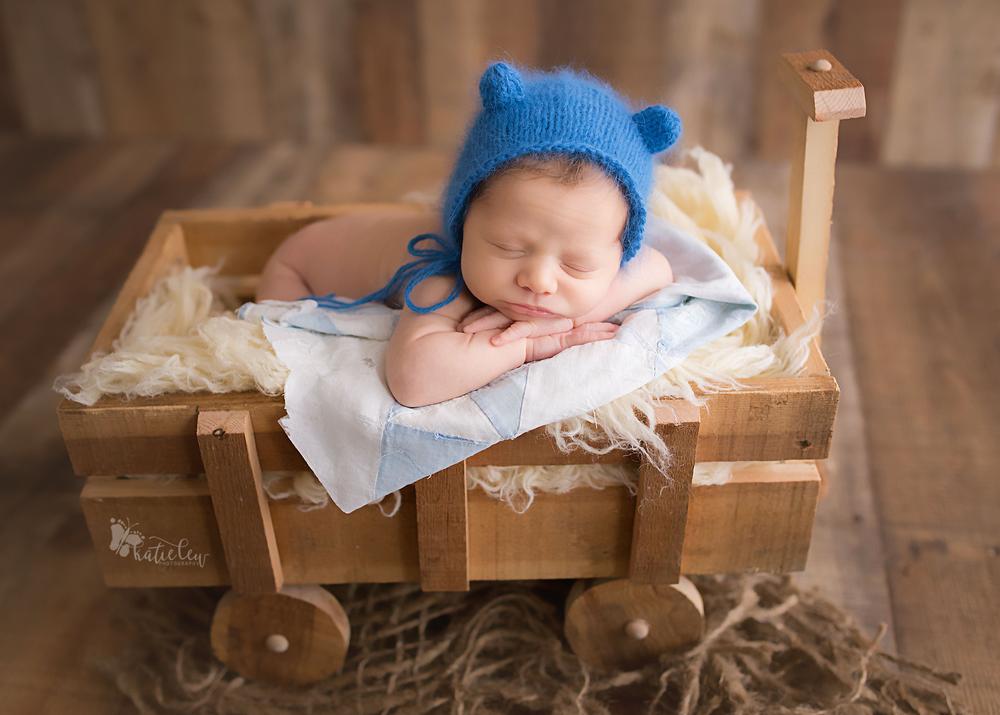 A newborn boy wearing a blue bear hat