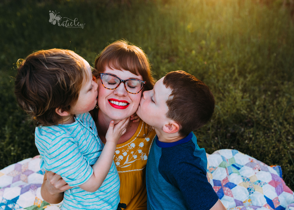 Two sons kissing their mother's face