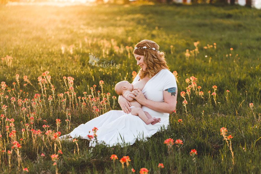 a mother wearing a floral crown and sitting in a bed of wildflowers nurses her baby